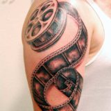 black and grey film roll tattoo
