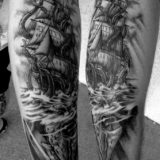 black and grey ship and squid tattoo