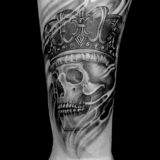 black and grey skull with crown tattoo