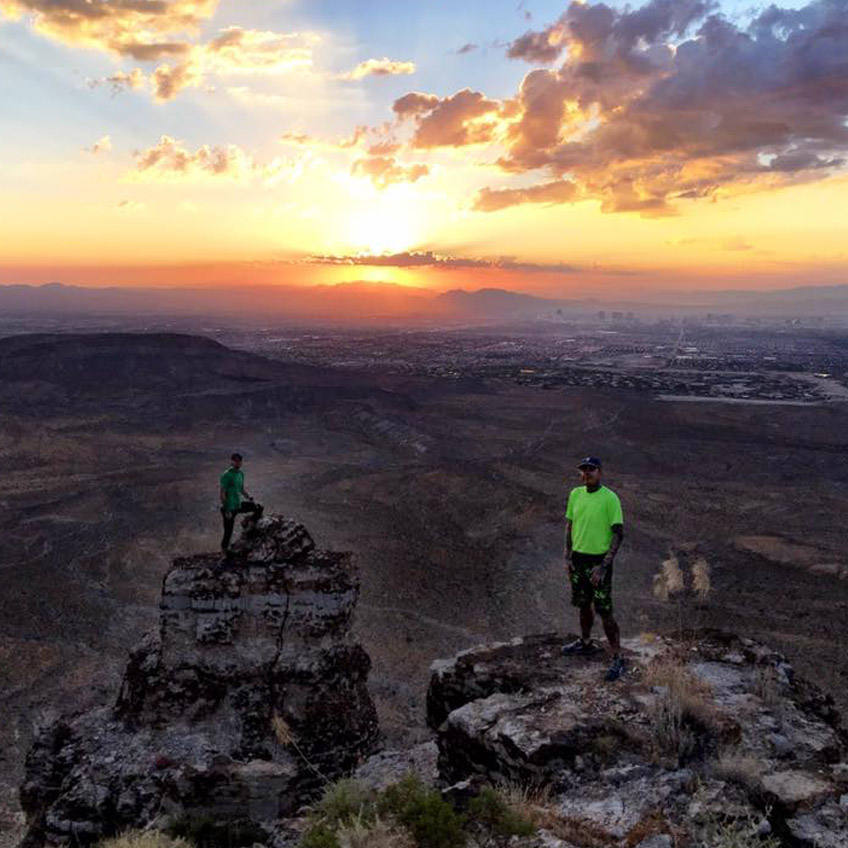 Two runners standing on top of Mt. Griffth summit in the Spring Mountains
