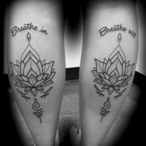lotus tattoo linework on each leg type reading breathe in and breathe out