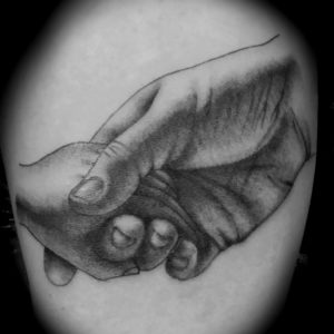 adult holding child's hand tattoo in black and grey