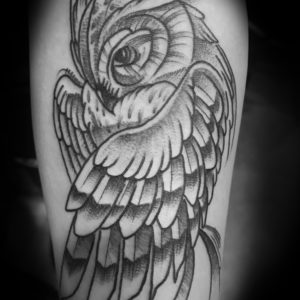 stylized black and grey owl tattoo