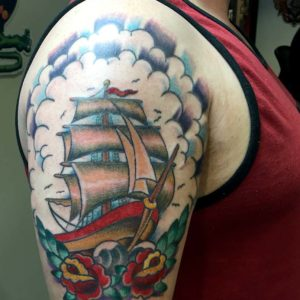 traditional ship tattoo on upper arm