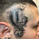 old english letter on head tattoo