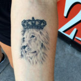 black and grey crowned lion tattoo