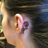 red rose behind ear tattoo