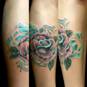 purple and teal rose tattoo on arm