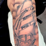 black and grey ship at sea tattoo