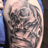 black and grey skull on book tattoo