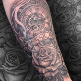 black and grey stopwatch and rose tattoo