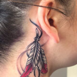 feathers behind ear tattoo