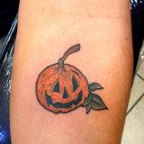 pumpkin tattoo on forearm
